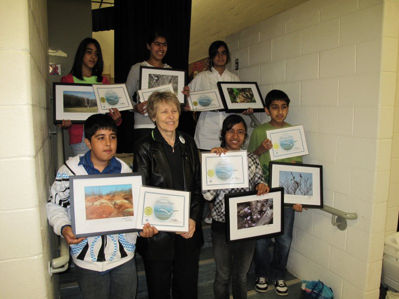 Dr Roberta Bondar with student winners  holding their certificates and framed winning submissions.