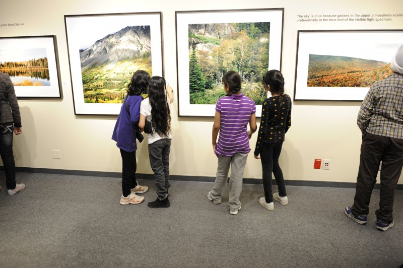 Elementary school students examine photographs in the Travelling Exhibition and Learning Experience