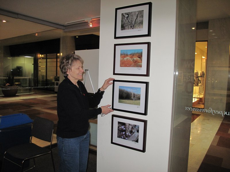 Dr. Bondar hanging student winning submissions in the Travelling Exhibition and Learning Experience at the First Canadian Place Gallery for public display.