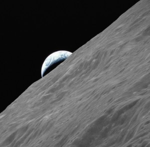 A crescent of Earth rises above the lunar horizon photographed from Apollo 17 in lunar orbit.